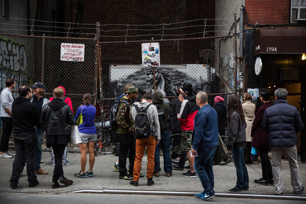 . People look at the latest work from street artist Banksy  on October 9, 2013 in the Lower East Side neighborhood of New York City. Banksy is in the midst of creating a month long series of pieces of street art.  (Photo by Andrew Burton/Getty Images)