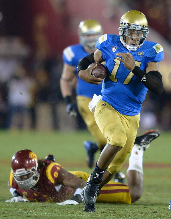. UCLA QB Brett Hundley gets yardage in the 4th quarter. UCLA defeated USC 35 to 14 in a matchup of cross town rivals at the Los Angeles Memorial Coliseum in Los Angeles, CA.  photo by (John McCoy/Los Angeles Daily News)