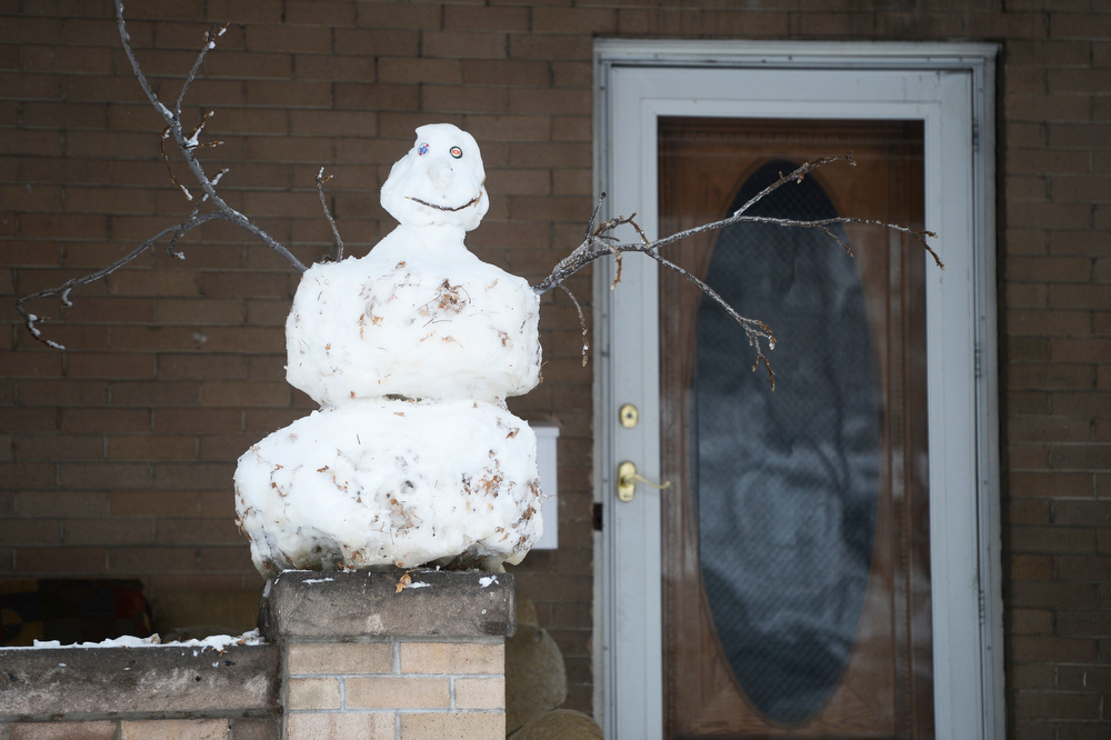 . A snowman perched on a patio near Dakota Ave and Downing St. Friday morning,  January 31, 2014. (Photo By Andy Cross / The Denver Post)