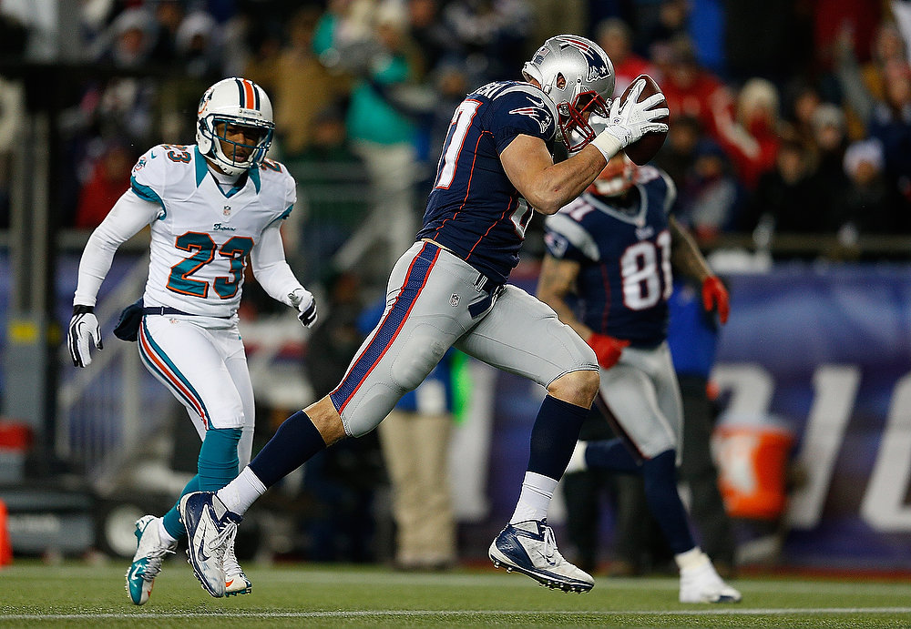 . Rob Gronkowski #87 of the New England Patriots runs the ball in for a touchdown despite the defense of Bryan McCann #23 of the Miami Dolphins in the second half at Gillette Stadium on December 30, 2012 in Foxboro, Massachusetts. (Photo by Jim Rogash/Getty Images)