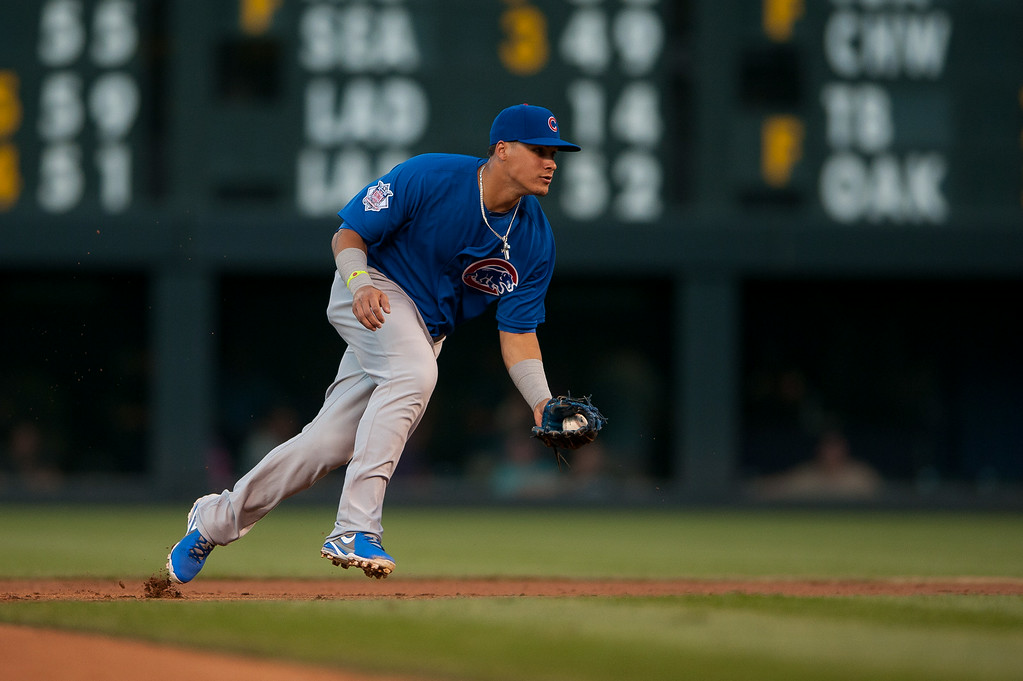 . DENVER, CO - AUGUST 06:  Javier Baez #9 of the Chicago Cubs fields a ground ball at second base before putting out the runner against the Colorado Rockies during a game at Coors Field on August 6, 2014 in Denver, Colorado.  (Photo by Dustin Bradford/Getty Images)