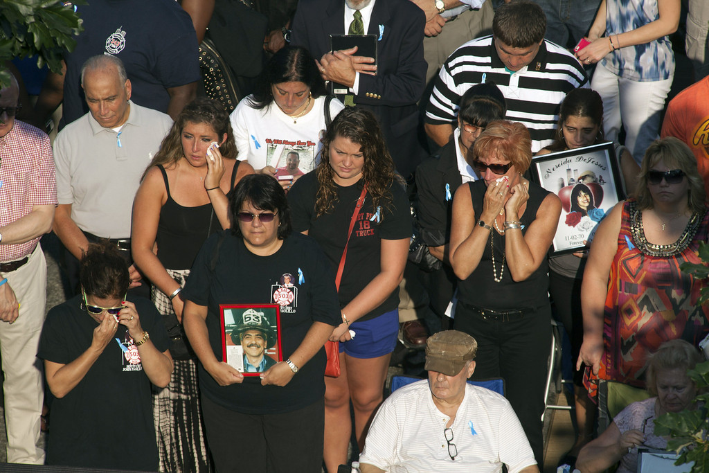 . Victims\' family members weep as they listen to their loved ones\' names being read at the 9/11 Memorial during ceremonies for the 12th anniversary of the terrorist attacks on lower Manhattan at the World Trade Center site on September 11, 2013 in New York City.   (Photo by Allan Tannenbaum-Pool/Getty Images)