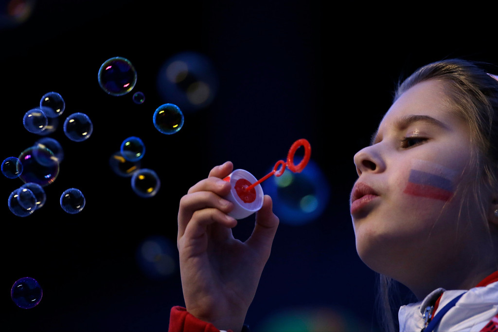 . A girl with a Russian flag painted on her face blows bubbles as she waits for the start of the closing ceremony of the 2014 Winter Olympics in Sochi, Russia, Sunday, Feb. 23, 2014. (AP Photo/Gregorio Borgia)