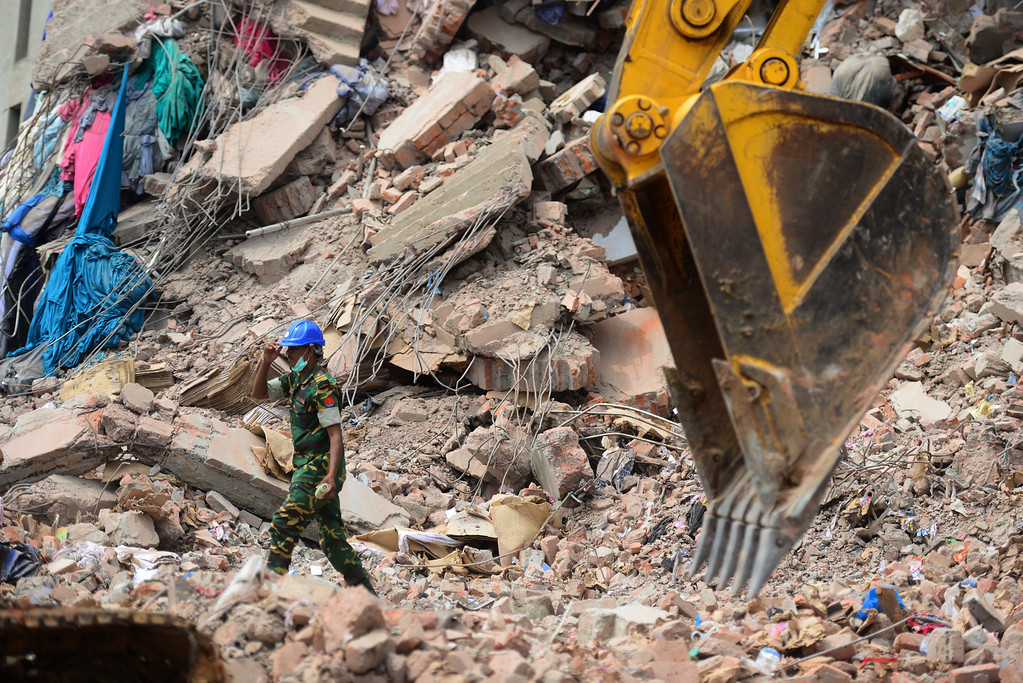 . A member of the Bangladesh Army operates an excavator to remove debris after an eight-storey building collapsed in Savar, on the outskirts of Dhaka, on April 30, 2013.    AFP PHOTO/MUNIR UZ ZAMAN/AFP/Getty Images
