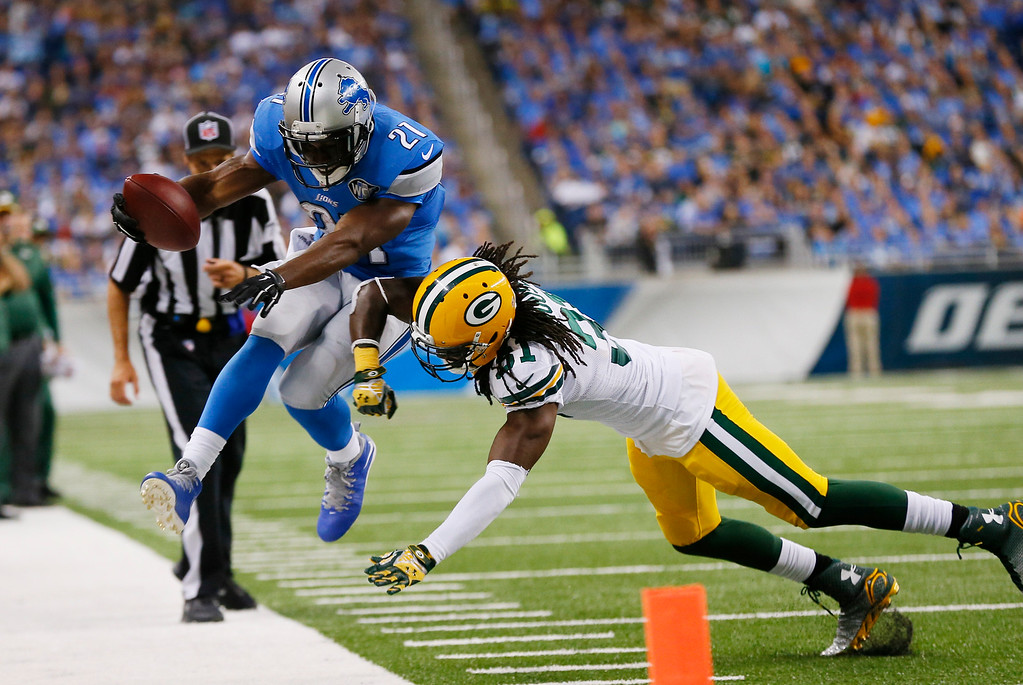 . Detroit Lions running back Reggie Bush (21) is pushed out of bounds by Green Bay Packers cornerback Davon House (31) during the first half of an NFL football game in Detroit, Sunday, Sept. 21, 2014. (AP Photo/Paul Sancya)