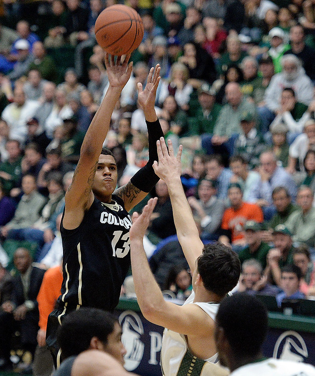 . CU\'s Dustin Thomas takes a shot over J.J. Avila during an NCAA game against CSU on Tuesday, Dec. 3, 2013, at the Moby Arena in Fort Collins. Jeremy Papasso/ Camera