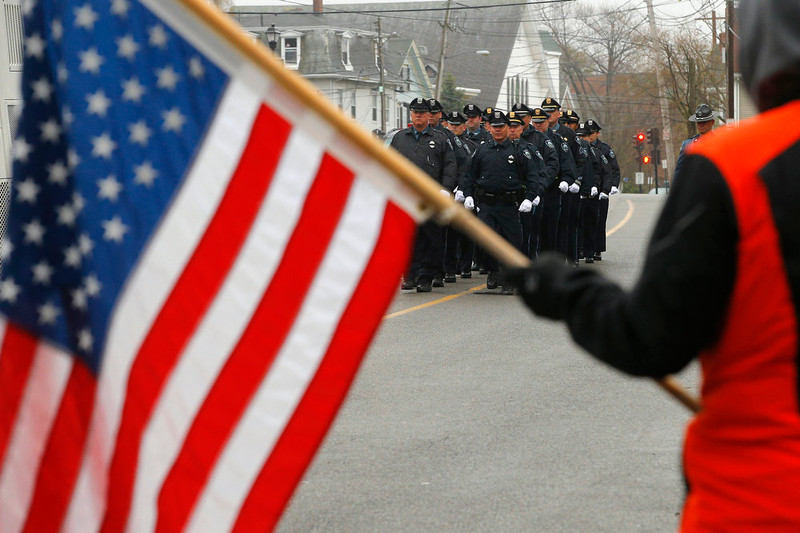 . Richard Corapi holds a U.S. flag from a sidewalk as Massachusetts Institute of Technology police officers march away from the funeral of fellow MIT police officer Sean Collier in Stoneham, Massachusetts April 23, 2013. Officer Collier was allegedly killed by the brothers accused of the Boston Marathon bombings, Dzhokhar and Tamerlan Tsarnaev. Two explosions hit the Boston Marathon April 15 killing at least three people and injuring over 100 others. REUTERS/Brian Snyder