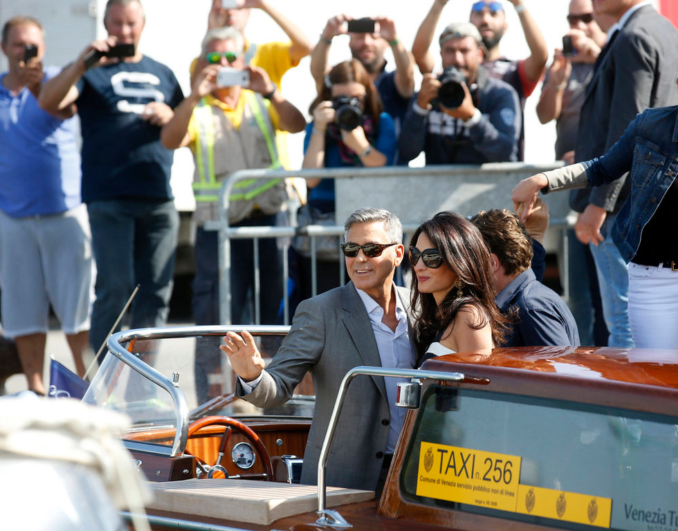 . George Clooney, left, and his fiancee Amal Alamuddin arrive in Venice, Italy, Friday, Sept. 26, 2014. Clooney, 53, and Alamuddin, 36, are expected to get married this weekend in Venice, one of the worldís most romantic settings. A clatch of photographers were on hand to record the coupleís arrival Friday at the Tronchetto terminal, where they were picked up by Clooneyís trusted water-taxi driver and taken to the luxury Cipriani hotel.  (AP Photo/Luca Bruno)