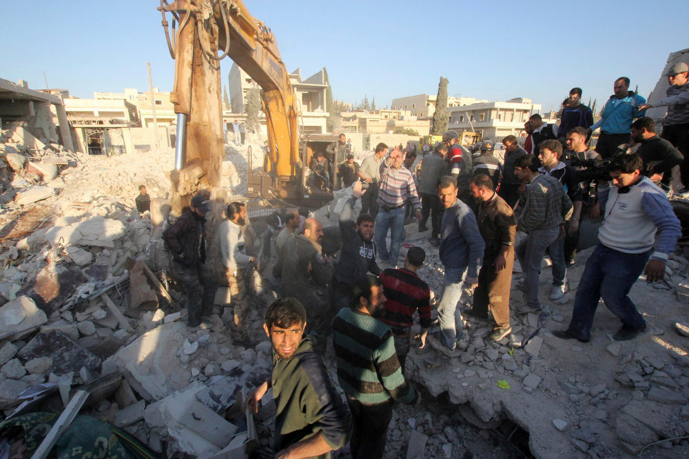 . People search for casualties under the rubble at a site hit by what activists say was a Scud missile in the town of Hretan, northeast of Aleppo March 29, 2013. REUTERS/ Giath Taha
