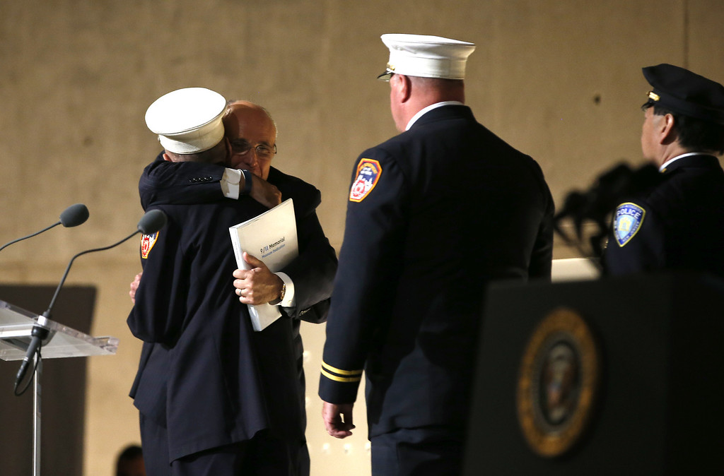 """. Former New York City Mayor Rudy Giuliani (back L) hugs retired New York City Fire fighter Mickey Kross as he greeted first responders to the scene of the World Trade Center attacks on September 11, 2001, during the opening ceremony for the National September 11 Memorial Museum at ground zero May 15, 2014 in New York City. The museum spans seven stories, mostly underground, and contains artifacts from the attack on the World Trade Center Towers on September 11, 2001 that include the 80 ft high tridents, the so-called \""""Ground Zero Cross,\"""" the destroyed remains of Company 21\'s New York Fire Department Engine as well as smaller items such as letter that fell from a hijacked plane and posters of missing  loved ones projected onto the wall of the museum. The museum will open to the public on May 21.  (Photo by Mike Segar-Pool/Getty Images)"""