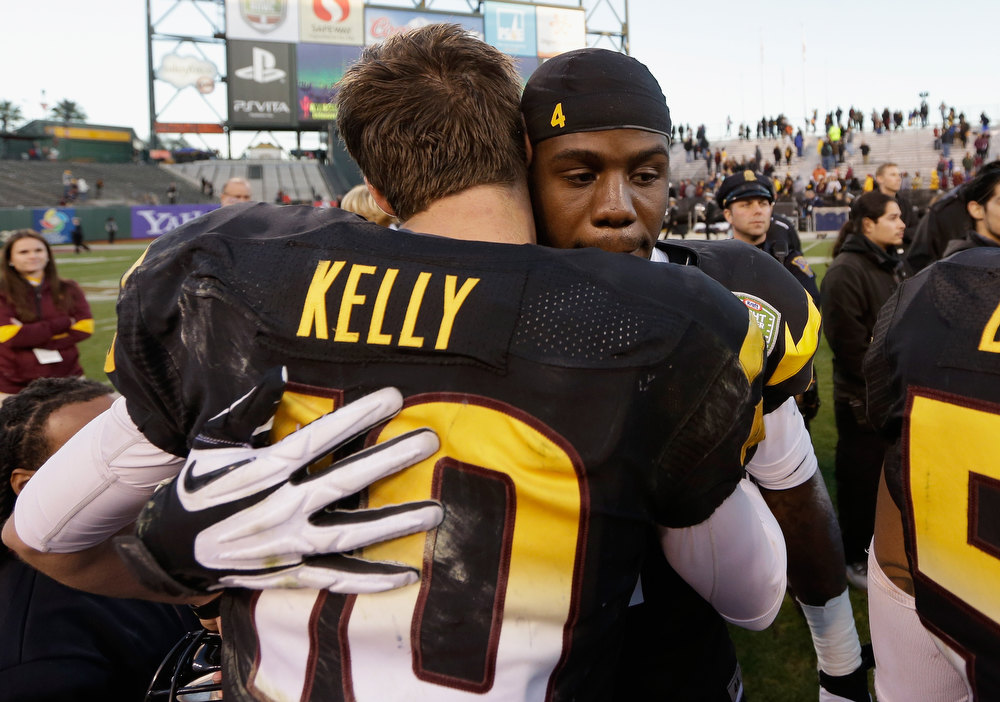 Description of . Taylor Kelly #10 congratulates Marion Grice #1 of the Arizona State Sun Devils after Grice was named offensive player of the game in their victory over the Navy Midshipmen in the Kraft Fight Hunger Bowl at AT&T Park on December 29, 2012 in San Francisco, California.  (Photo by Ezra Shaw/Getty Images)