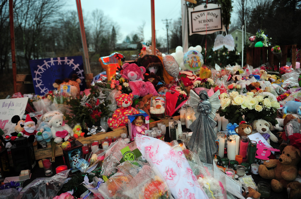 . Offerings stand at a makeshift shrine to the victims of an elementary school shooting in Newtown, Connecticut, December 17, 2012.  Funerals began Monday in the little Connecticut town of Newtown after the school massacre that took the lives of 20 small children and six staff, triggering new momentum for a change to America\'s gun culture. The first burials, held under raw, wet skies, were for two six-year-old boys who were among those shot in Sandy Hook Elementary School. On Tuesday, the first of the girls, also aged six, was due to be laid to rest. There were no Monday classes at all across Newtown, and the blood-soaked elementary school was to remain a closed crime scene indefinitely, authorities said. AFP PHOTO/Emmanuel DUNAND  DUNAND/AFP/Getty Images