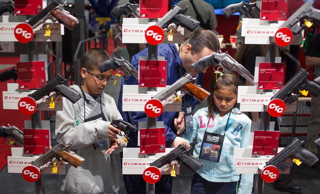 . Family members look at hand guns at the George R. Brown Convention Center, the site for the National Rifle Association\'s annual meeting in Houston, Texas on May 4, 2013. Organizers expect some 70,000 attendees at the 142nd NRA Annual Meetings & Exhibits in Houston, which began on Friday and continues through Sunday. REUTERS/Adrees Latif