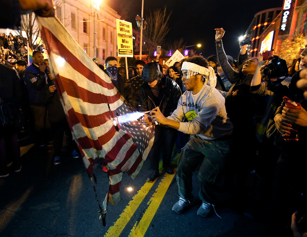 . A protestor uses a lighter and an aerosol can to burn one of two American flags during a protest in the Chinatown area of Washington, Tuesday, Nov. 25, 2014. A grand jury in Ferguson, Mo., on Monday, Nov. 24th, 2014, declined to indict police officer Darren Wilson in the shooting death of Michael Brown, an unarmed African-American man. (AP Photo/Alex Brandon)