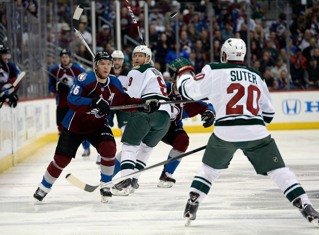 . Minnesota Wild defenseman Ryan Suter (20) reaches up to glove the puck as Colorado Avalanche center Paul Stastny (26) keeps his eye on it during the first period.   (Photo by John Leyba/The Denver Post)