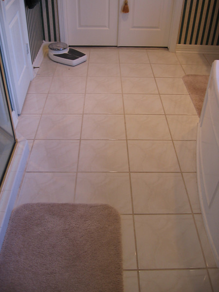 The white porcelain tile floor is slippery, and it might clash with the darker granite counter tops, so the floor must go too.