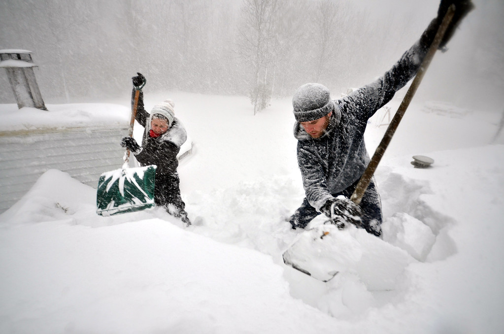 . BUFFALO, NY - NOVEMBER 20, 2014: Tami Normile and Richard Brooks attempt to remove some of the five feet of snow from a roof top on November 20, 2014 in the Lakeview neighborhood of Buffalo, New York.The record setting Lake effect snowstorm dumped up to six feet of snow in less than 24 hours closing a one hundred mile section of The New York State Thruway as well as other major roads around Buffalo. Seven deaths have already been  attributed to the storm and a second round beginning late Wednesday evening will bring up to three more feet of snow overnight and into Thursday.  (Photo by John Normile/Getty Images)