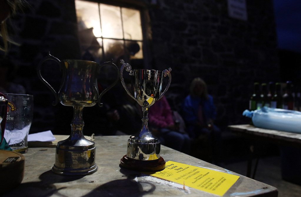 . CADGWITH, ENGLAND - SEPTEMBER 05:  Trophies are displayed as people gather for the prizegiving after taking part in the final Cadgwith Cove fortnightly fishing competition of the year, in Cadgwith on September 5, 2013 in Cornwall, England. The summertime competition to catch the heaviest fish of a chosen type, (for this final the fish was bass) allows locals and visitors the chance to fish for fun and a cash prize, with the catch cooked in a pot at the end of the night on some occasions. Set on the Lizard peninsula in Cornwall, the village of Cadgwith, which was established in medieval times, owes its existence to the fishing industry. However, whilst fishing remains an important part of village life today, tourism is also now a major source of income for the inhabitants. (Photo by Matt Cardy/Getty Images)
