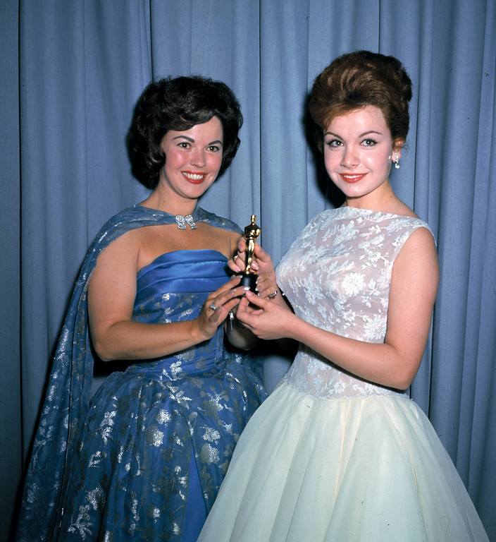 . Actress Annette Funicello, right, and former child film star Shirley Temple, left, are seen holding a miniature Oscar statuette at the annual Academy Awards presentations, in Los Angeles, Calif., in April 1961. (AP Photo/Brich)