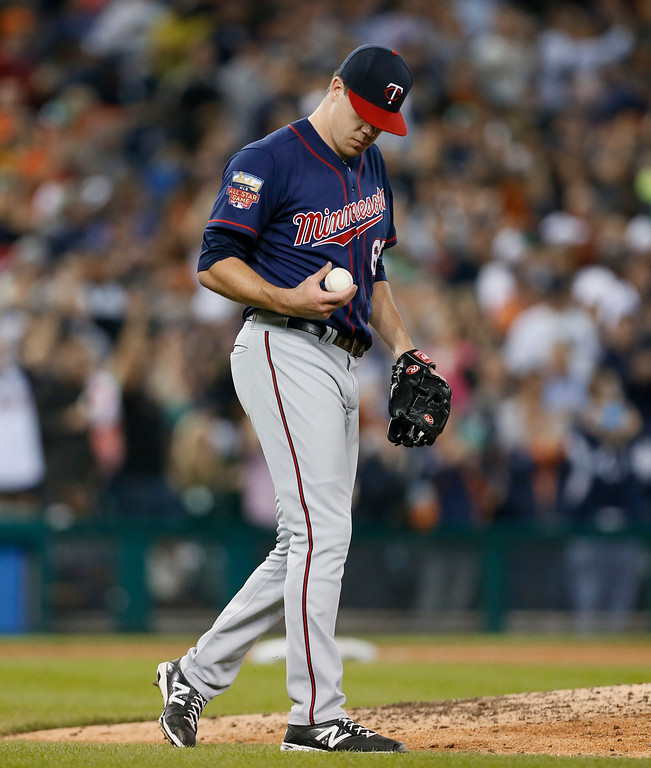 . Minnesota Twins starting pitcher Trevor May looks at a ball after allowing a solo home run to Detroit Tigers\' Miguel Cabrera in the the fourth inning of a baseball game in Detroit, Thursday, Sept. 25, 2014. (AP Photo/Paul Sancya)
