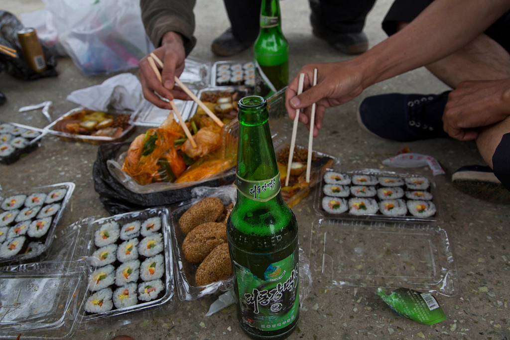 """. In this June 16, 2014 photo, North Korean men share a picnic lunch and North Korean-brewed and bottled Taedonggang beer along the road in North Korea\'s North Hwanghae province. The Associated Press was granted permission to embark on a weeklong road trip across North Korea to the countryís spiritual summit Mount Paektu. The trip was on North Korea\'s terms. An AP reporter and photographer couldn\'t interview ordinary people or wander off course, and government \""""minders\"""" accompanied them the entire way. (AP Photo/David Guttenfelder)"""