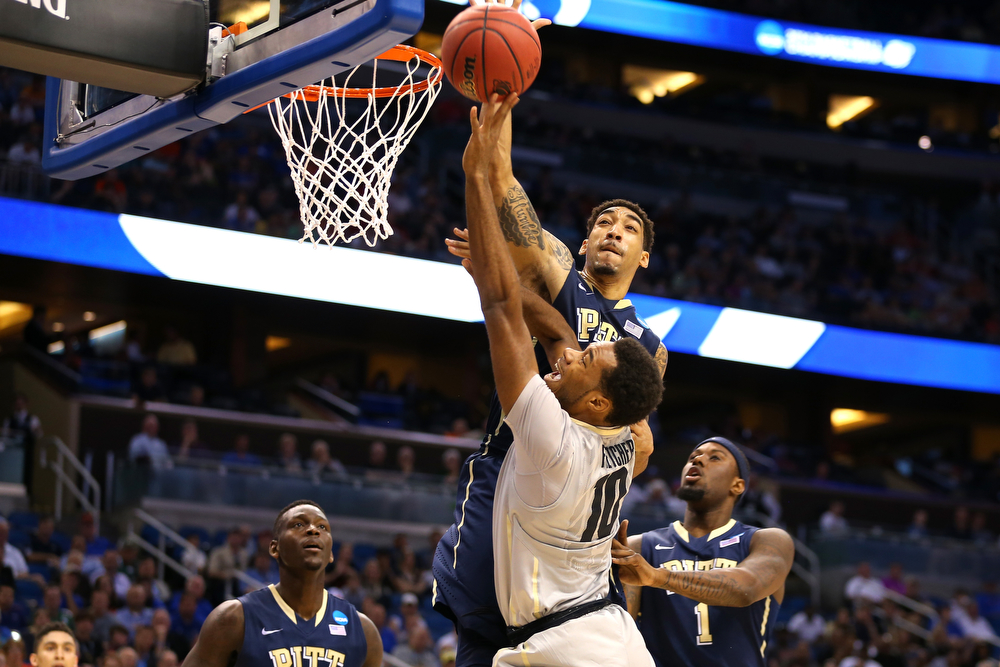 . Cameron Wright #3 of the Pittsburgh Panthers goes up for a block against Tre\'Shaun Fletcher #10 of the Colorado Buffaloes in the first half during the second round of the 2014 NCAA Men\'s Basketball Tournament at Amway Center on March 20, 2014 in Orlando, Florida.  (Photo by Mike Ehrmann/Getty Images)
