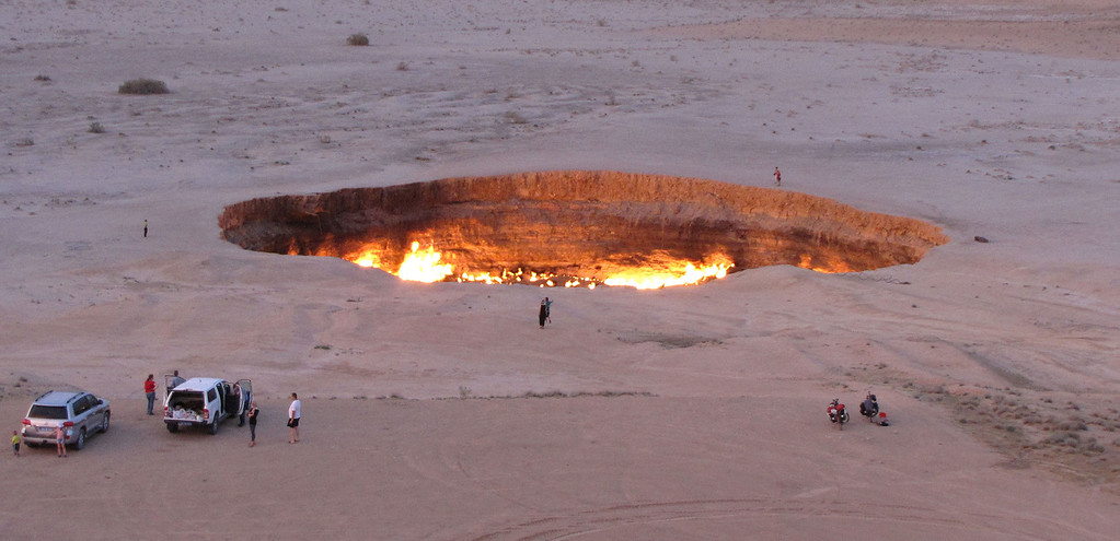 ". A picture taken on May 3, 2014, shows people visiting ""The Gateway to Hell,\"" a huge burning gas crater in the heart of Turkmenistan\'s Karakum desert. The fiery pit was the result of a simple miscalculation by Soviet scientists in 1971 after their boring equipment suddenly drilled through into an underground cavern and a deep sinkhole formed. Fearing that the crater would emit poisonous gases, the scientists took the decision to set it alight, thinking that the gas would burn out quickly and this would cause the flames to go out. But the flames have not gone out in more than 40 years, in a potent symbol of the vast gas reserves of Turkmenistan, which are believed to be the fourth largest in the world.  AFP PHOTO / IGOR  SASIN/AFP/Getty Images"