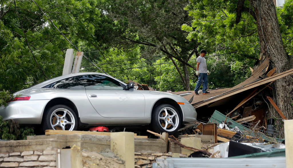 . A man looks through debris at a home recently destroyed by flood waters along the Blanco River, Tuesday, May 26, 2015, in Wimberley, Texas. Authorities say recovery teams continue to search for as many as a dozen missing people in an area where punishing rains have destroyed or damaged more than 1,000 homes and killed at least three people statewide this past weekend. (AP Photo/Eric Gay)