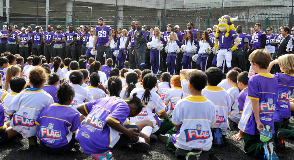 . Minnesota Vikings head coach Leslie Frazier, center, joined by Adrian Peterson and Jared Allen, addresses children at the clinic. (NFL: Sean Ryan)
