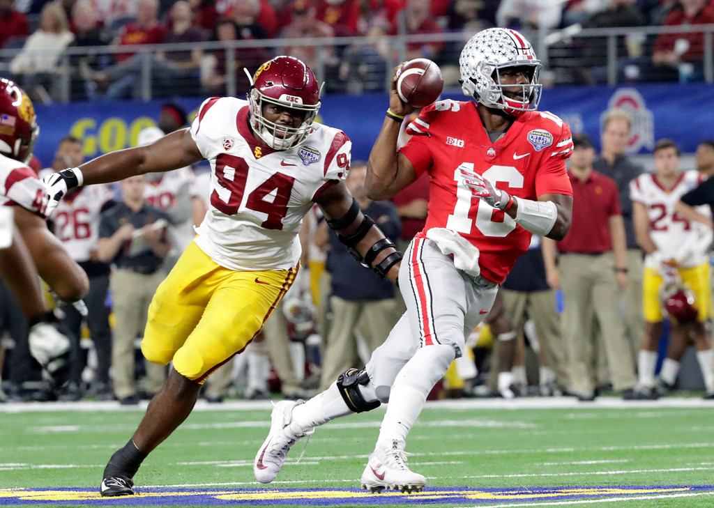 . Ohio State quarterback J.T. Barrett (16) is chased by Southern California defensive tackle Rasheem Green (94) during the first half of the Cotton Bowl NCAA college football game in Arlington, Texas, Friday, Dec. 29, 2017. (AP Photo/LM Otero)