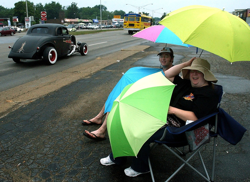 . Steady rain didn\'t stop John Drolet and Ellen Klausmeyer from enjoying the 16th Annual Woodward Dream Cruise in Royal Oak. (Oakland Press Photo/Vaughn Gurganian)