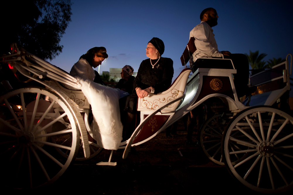 Description of . An Ultra-Orthodox Jewish bride, left, arrives for her wedding ceremony in Netanya, Israel, Wednesday, Jan. 2, 2013. Thousands of people attended the wedding. (AP Photo/Oded Balilty)