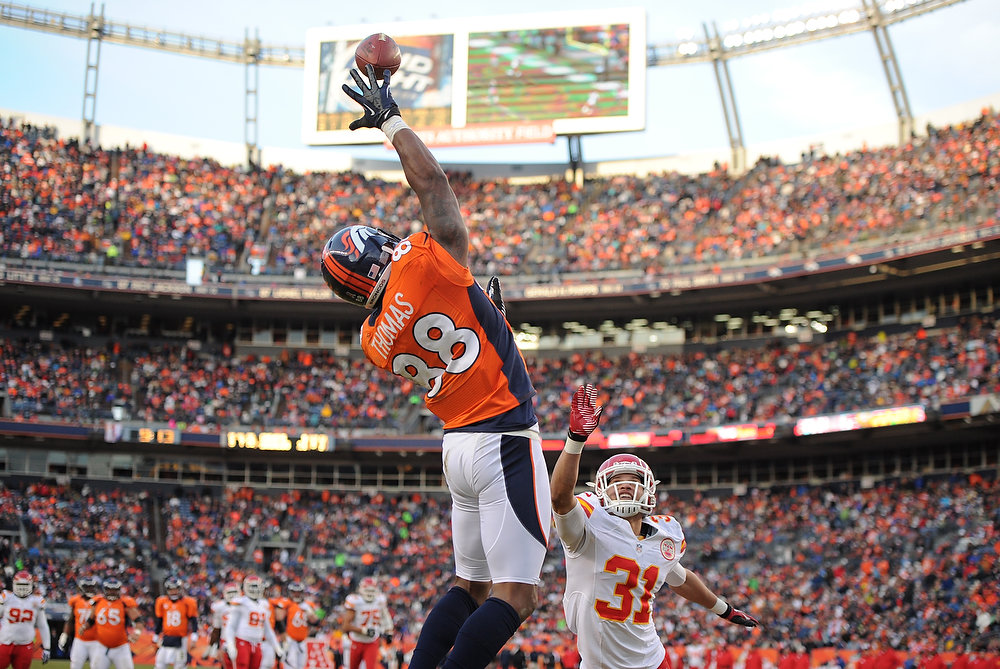 Description of . Denver Broncos wide receiver Demaryius Thomas (88) reaches up for the ball and catches it for a touchdown over Kansas City Chiefs free safety Tysyn Hartman (31) during the third quarter. The Denver Broncos vs Kansas City Chiefs at Sports Authority Field Sunday December 30, 2012. Joe Amon, The Denver Post