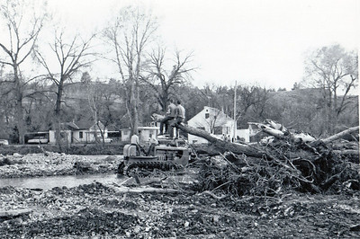 Perched on the trunk of an uprooted tree, two boys watch as workers remove debris.  May 1965 flood - Spearfish, SD.  We're uncertain as to this location.  Please send us an e-Mail if you can help us.