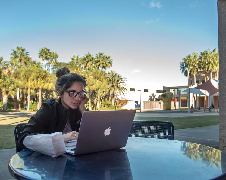 Student Selina Velasquez studies for her final exam in the Center for Instruction courtyard.