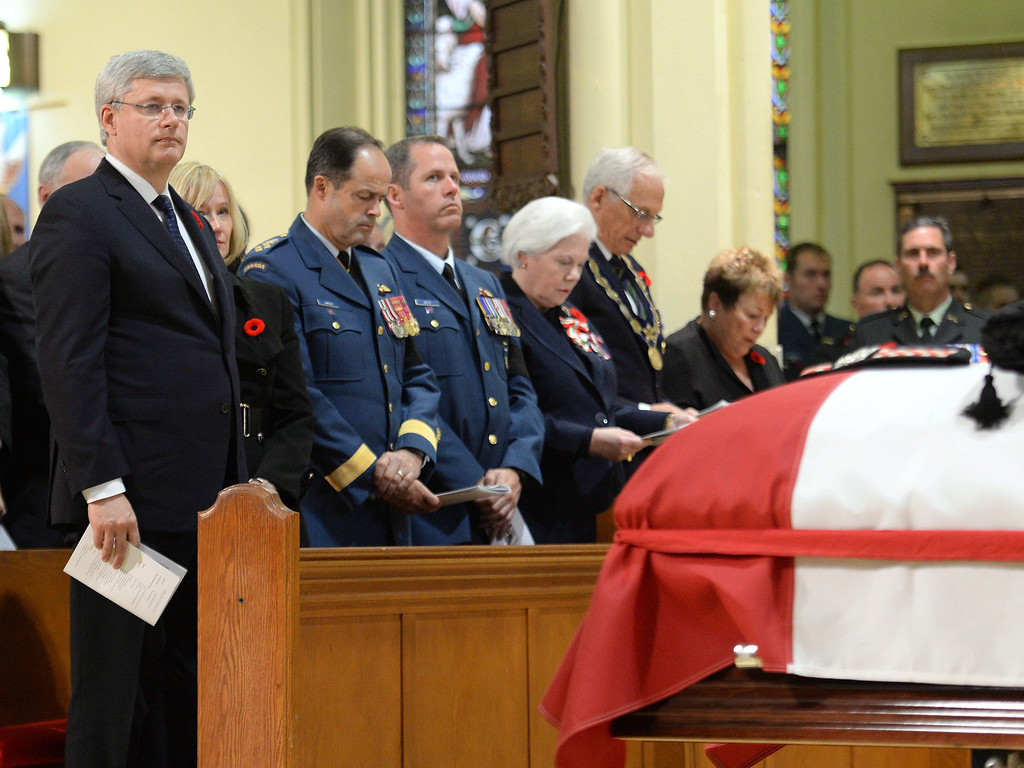 . Prime Minister Stephen Harper rises as the coffin of Cpl. Nathan Cirillo is arrives at his regimental funeral service in Hamilton, Ontario,  on Tuesday, Oct. 28, 2014.   (AP Photo/The Canadian Press, Nathan Denette)