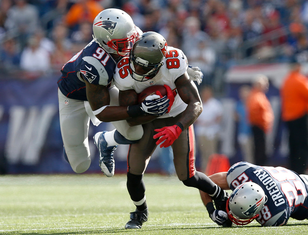 . New England Patriots outside linebacker Jamie Collins (91) and strong safety Steve Gregory (28) tackle Tampa Bay Buccaneers wide receiver Kevin Ogletree (85) in the second half of an NFL football game Sunday, Sept. 22, 2013, in Foxborough, Mass. (AP Photo/Elise Amendola)