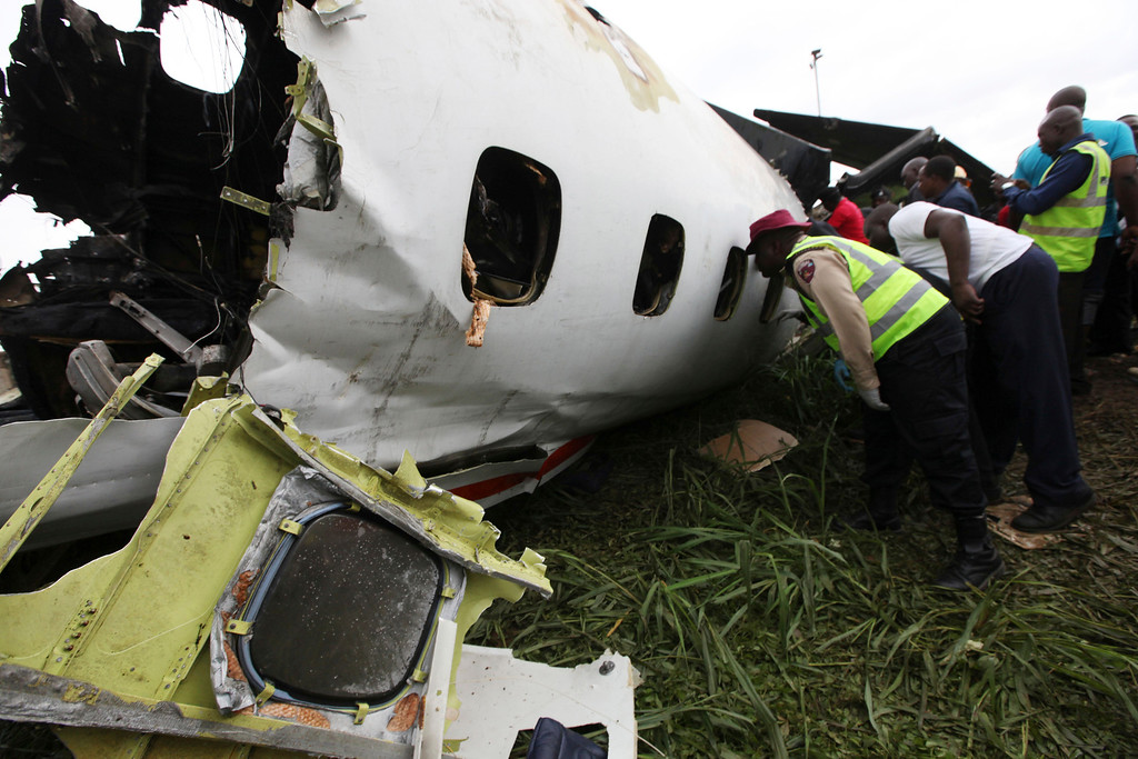 . Rescue workers peer into the wreckage of a charter passenger jet which crashed soon after take off from Lagos airport, Nigeria, Thursday, Oct. 3, 2013.  (AP Photo/Sunday Alamba)