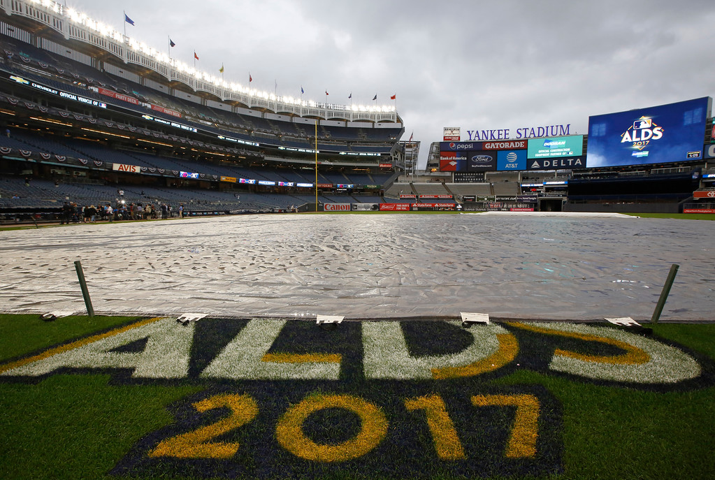 . A wet tarp remained on the field during time originally scheduled for batting practice before an American League Division Series baseball game between the New York Yankees and the Cleveland Indians in New York, Monday, Oct. 9, 2017. Predicted rain showers threatened to delay the game. (AP Photo/Kathy Willens)