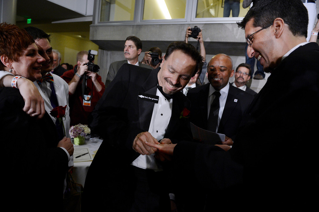 . DENVER, CO. - MAY 01: David Westman struggles putting a ring on Anthony Aragon\'s finger during their civil union ceremony at the Webb Building in  Denver CO, May 01, 2013.  The Clerk and Recorder\'s Office opened for business from midnight to 3 a.m. to issue civil union licenses to couples on May 01, 2013 when the Civil Union Act became law. One Colorado offered a civil-union celebration for couples in the building\'s atrium from midnight to 2 a.m., as judges, magistrates and other officiants performed the ceremonies. Colorado became the latest state to recognize the legal rights of same-sex couples � through marriage or civil unions � when Gov. John Hickenlooper signed state Senate Bill 11 into law March 21. (Photo By Craig F. Walker/The Denver Post)