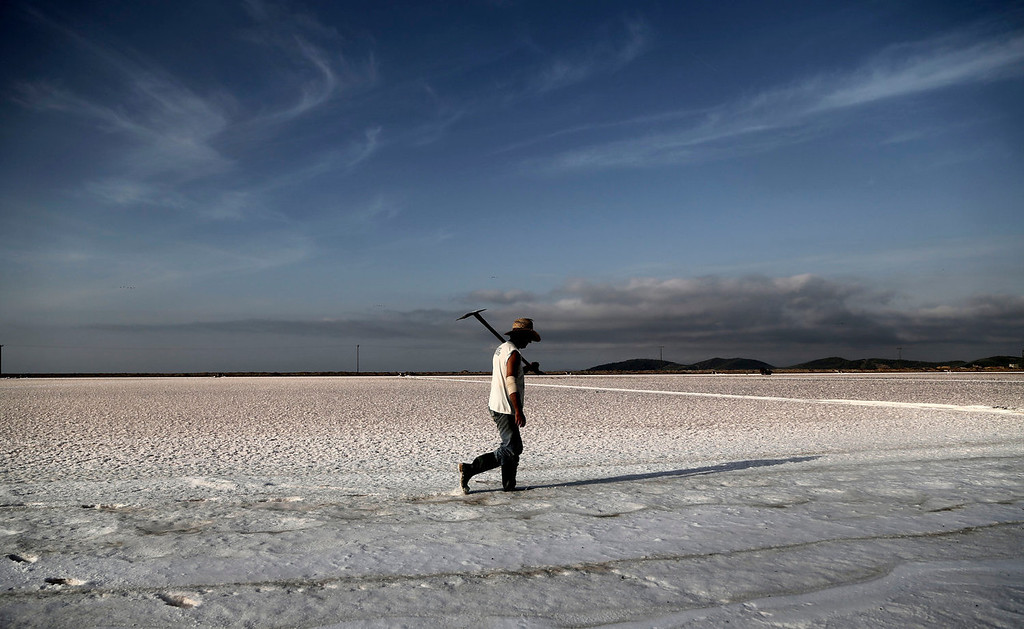 . A worker holding his shovel walks on a salt lake to a production site in Messolongi, western Greece. The facilities at the site are the largest saltworks in Greece, and are located at a protected wetland complex of estuaries and lagoons. (AP Photo/Dimitri Messinis)
