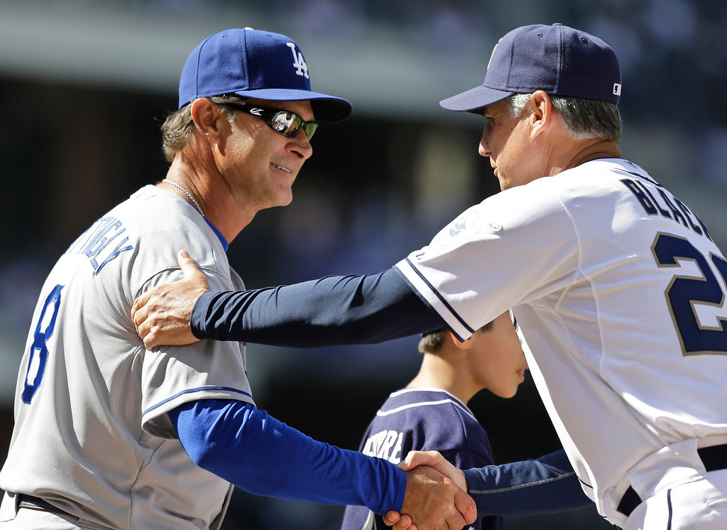 . Los Angeles Dodgers manager Don Mattingly and San Diego Padres manager Buddy Black greet each other during introductions prior to the home opener baseball game for the Padres in San Diego, Tuesday, April 9, 2013. (AP Photo/Lenny Ignelzi)