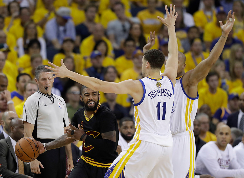 . Cleveland Cavaliers guard Kyrie Irving, left, is guarded by Golden State Warriors guard Klay Thompson (11) and forward David West during the first half of Game 2 of basketball\'s NBA Finals in Oakland, Calif., Sunday, June 4, 2017. (AP Photo/Marcio Jose Sanchez)