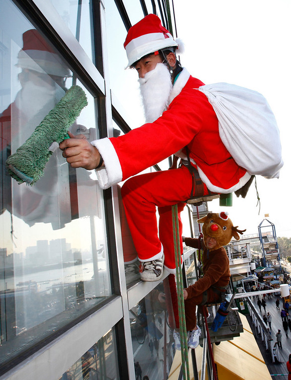 . Junya Kono, left, and Tomoharu Fujimaki, window cleaner dressed as Santa Claus and reindeer clean a window at a shopping mall in Tokyo, Japan, Wednesday, Dec. 23, 2009. (AP Photo/Shizuo Kambayashi)