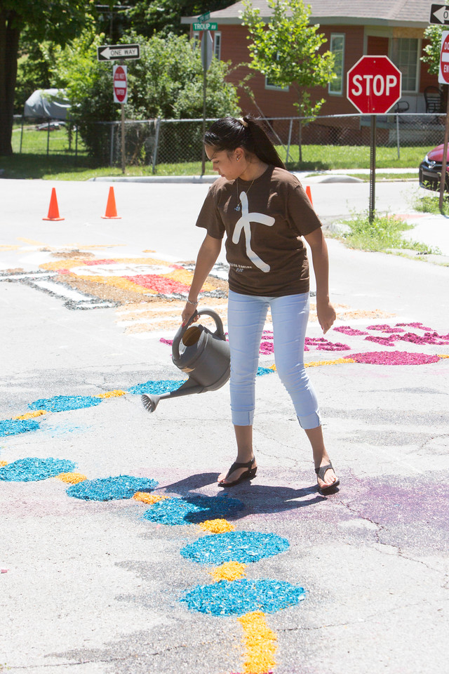 Jessica Carpio, St. Mary's senior, wets down the colored saw dust to keep it from blowing away.