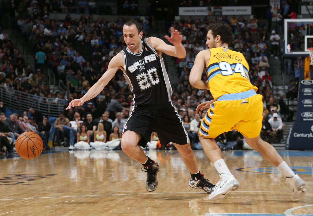 . San Antonio Spurs guard Manu Ginobili, left, of Argentina, pursues a loose ball with Denver Nuggets guard Evan Fournier, of France, in the third quarter of the Spurs\' 133-102 victory in an NBA basketball game in Denver, Friday, March 28, 2014. (AP Photo/David Zalubowski)
