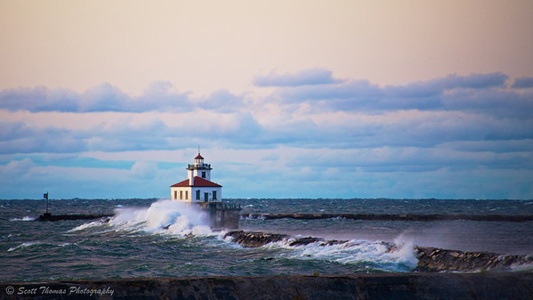 Waves collide with the Oswego Harbor breakwall near the West Pierhead Lighthouse in Oswego, New York.