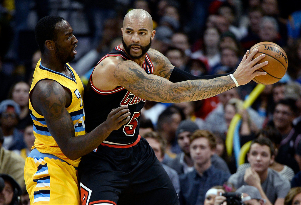 . Chicago Bulls power forward Carlos Boozer (5) holds the ball away from Denver Nuggets power forward J.J. Hickson (7) during the first quarter November 21, 2013 at Pepsi Center. (Photo by John Leyba/The Denver Post)