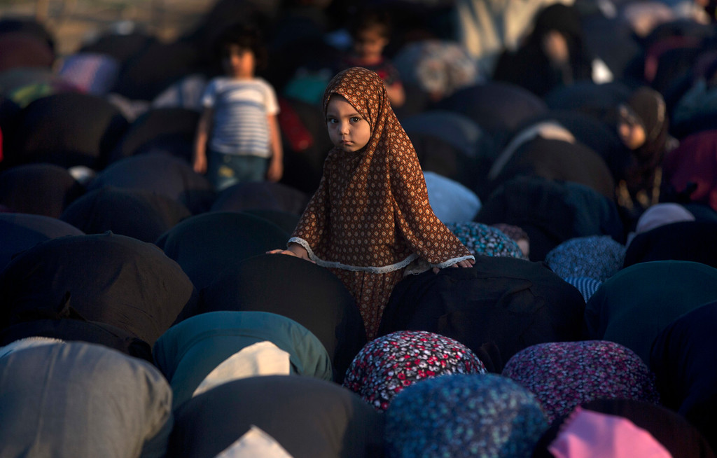 . A Palestinian girl stands in the middle of Muslim women performing Eid al-Fitr prayers, marking the end of the holy fasting month of Ramadan, in Eastern Gaza City, Friday, June 15, 2018. (AP Photo/Khalil Hamra)