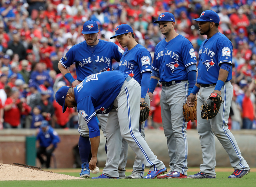 . Toronto Blue Jays\' Francisco Liriano leans over to grab the rosin bag as, from left rear, Josh Donaldson, Darwin Barney, Troy Tulowitzki and Edwin Encarnacion, right, stand by him after he was hit on the back of the head by a single off the bat of Texas Rangers\' Carlos Gomez in the eighth inning of Game 2 of baseball\'s American League Division Series, Friday, Oct. 7, 2016, in Arlington, Texas. Liriano was taken out of the game after the incident. (AP Photo/David J. Phillip)